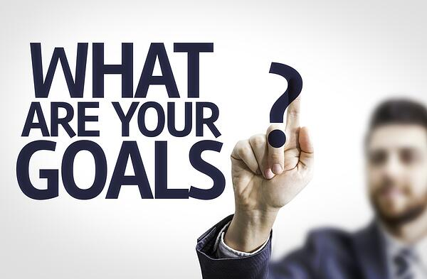 Business man pointing to transparent board with text What are Your Goals?-1