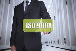 Businessman in a data center selecting a green label with iso 9001 written on it-1