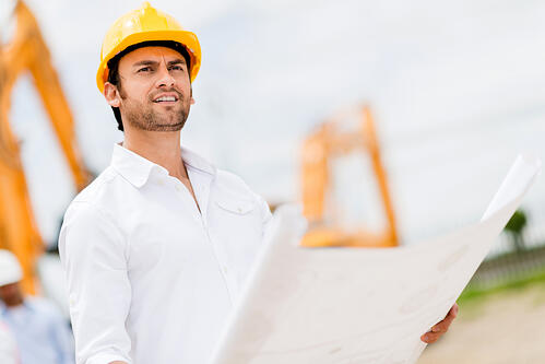 Engineer looking at blueprints at a construction site