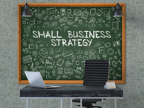 Small Business Strategy. Green Chalkboard on the Gray Concrete Wall in the Interior of a Modern Office with Hand Drawn Small Business Strategy. Business Concept with Doodle Style Elements. 3D.