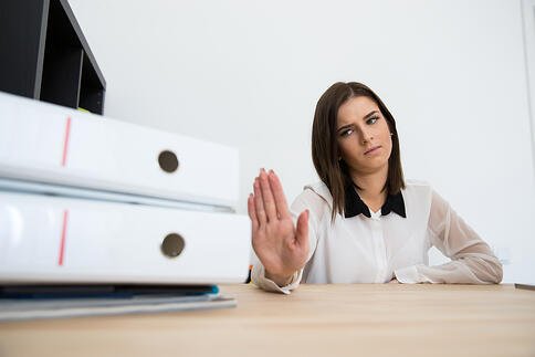 Young businesswoman sitting at the table and saying - No